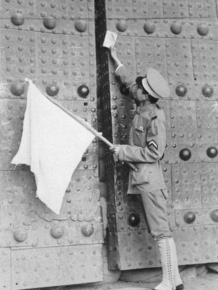 1937年7月31日,宛平城门处,一名举着白旗的中国士兵通过城门缝隙将日军的投降条件书塞入城内。(图源:VCG)